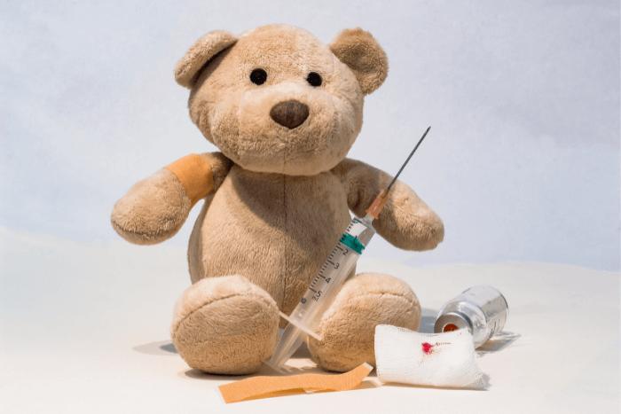 Λούτρινο αρκουδάκι που έχει πάνω του μια σύριγγα εμβολίου και δίπλα του φιαλίδιο με φάρμακο εμβολίου, μια γάζα κι ένας τραυμοπλάστ.