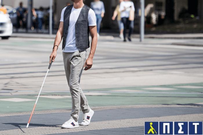 Άνδρας με λευκό μπαστούνι περπατάει. Κάτω δεξιά το λογότυπο του Πανελληνίου Συνδέσμου Τυφλών.