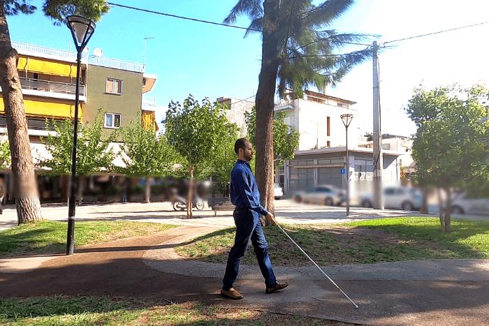 Ο Βαγγέλης Αγουλάς περπατάει με το λευκό μπαστούνι σε πλατεία
